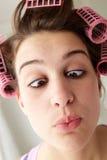 Adolescente con el pelo en los bigudíes que tiran de una cara Imágenes de archivo libres de regalías