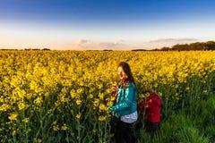 Adolescente con el pelo largo en campo amarillo del bittercress Foto de archivo libre de regalías