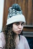 Adolescente con el pelo largo y rizado que lleva un sombrero de punto Imagenes de archivo