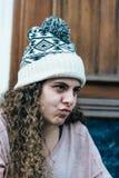 Adolescente con el pelo largo y rizado que lleva un sombrero de punto Imágenes de archivo libres de regalías