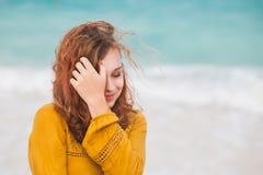 Adolescente con el pelo rojo en la costa del océano Imagen de archivo libre de regalías