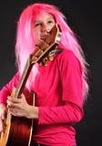 Adolescente con el pelo rosado que toca la guitarra Imagen de archivo
