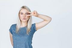 Adolescente con el pelo rubio que muestra el signo de la paz Imagenes de archivo