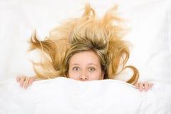 Adolescente con el pelo salvaje en cama Fotos de archivo