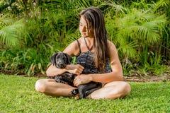 Adolescente con el perrito negro de Labrador Imagen de archivo