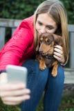 Adolescente con el perro basset del animal doméstico que presenta para Selfie Fotos de archivo