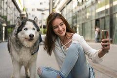 Adolescente con el perro en la ciudad que hace el selfie Imagenes de archivo