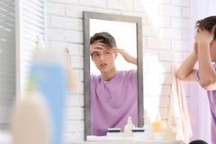 Adolescente con el problema del acné que mira en espejo Imagen de archivo libre de regalías