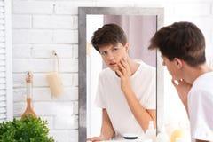 Adolescente con el problema del acné que mira en espejo Fotos de archivo libres de regalías