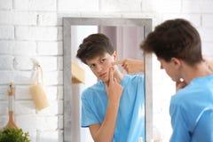 Adolescente con el problema del acné que mira en espejo Imagen de archivo
