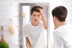 Adolescente con el problema del acné que mira en espejo Imagenes de archivo