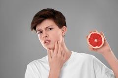 Adolescente con el problema del acné que sostiene el pomelo Imagen de archivo
