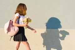 Adolescente con el ramo, mochila Va contra la pared gris, espacio de la copia Foto de archivo libre de regalías