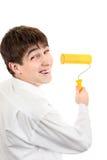 Adolescente con el rodillo de pintura Imagen de archivo libre de regalías