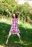 Adolescente con el salto aumentado brazos en naturaleza Fotos de archivo