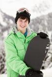 Adolescente con el Snowboard el día de fiesta del esquí Foto de archivo