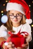 Adolescente con el sombrero de Papá Noel que lleva a cabo un presente Fotos de archivo libres de regalías