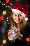 Adolescente con el sombrero de Papá Noel que sostiene decoraciones de la Navidad Fotos de archivo