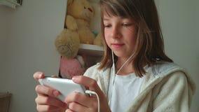 Adolescente con el teléfono a disposición y auriculares, niños y tecnología moderna almacen de metraje de vídeo