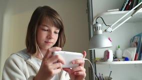 Adolescente con el teléfono a disposición y auriculares, niños y tecnología moderna metrajes