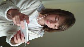 Adolescente con el teléfono a disposición y auriculares, niños y tecnología moderna V?deo vertical metrajes