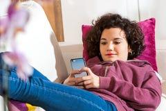 Adolescente con el teléfono elegante en el sofá. Foto de archivo libre de regalías