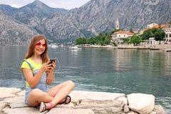 Adolescente con el teléfono elegante el vacaciones de verano Imágenes de archivo libres de regalías