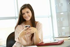 Adolescente con el teléfono en clase Imagen de archivo libre de regalías