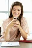 Adolescente con el teléfono en clase Fotografía de archivo libre de regalías