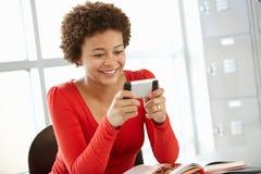Adolescente con el teléfono en clase Foto de archivo libre de regalías