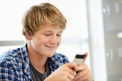 Adolescente con el teléfono en clase Fotos de archivo libres de regalías
