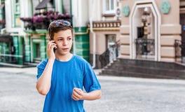 Adolescente con el teléfono en la calle Foto de archivo