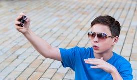 Adolescente con el teléfono en la calle Imagen de archivo libre de regalías