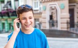 Adolescente con el teléfono en la calle Imagenes de archivo