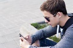 Adolescente con el teléfono en la calle Fotos de archivo