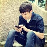 Adolescente con el teléfono móvil al aire libre Imagen de archivo