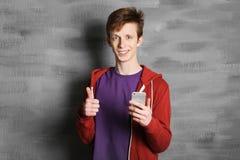 Adolescente con el teléfono móvil cerca de la pared Fotografía de archivo libre de regalías