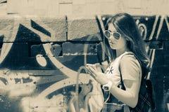 Adolescente con el teléfono móvil cerca de la pared de la pintada Imagen de archivo
