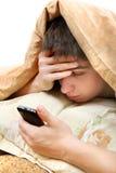 Adolescente con el teléfono móvil en la cama Fotografía de archivo libre de regalías