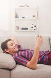 Adolescente con el teléfono móvil en sala de estar en casa Foto de archivo libre de regalías