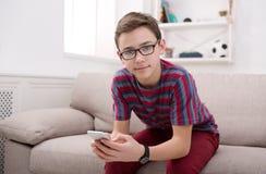 Adolescente con el teléfono móvil en sala de estar en casa Imágenes de archivo libres de regalías