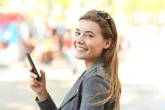Adolescente con el teléfono móvil que mira la cámara Foto de archivo libre de regalías