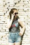Adolescente con el teléfono móvil y las gafas de sol Fotos de archivo libres de regalías