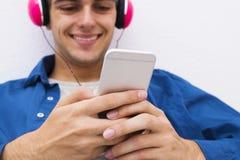 Adolescente con el teléfono móvil y los auriculares Imagen de archivo