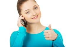 Adolescente con el teléfono móvil y los pulgares para arriba Imágenes de archivo libres de regalías