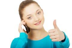 Adolescente con el teléfono móvil y los pulgares para arriba Fotografía de archivo