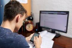 Adolescente con el teléfono móvil y el ordenador Imagen de archivo libre de regalías