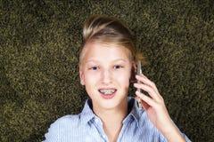 Adolescente con el teléfono Tener el adolescente de la diversión miente en una alfombra Imagen de archivo