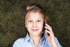 Adolescente con el teléfono Tener el adolescente de la diversión miente en una alfombra Imagen de archivo libre de regalías