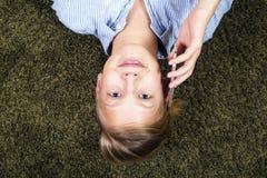 Adolescente con el teléfono Tener el adolescente de la diversión miente en una alfombra Fotografía de archivo
